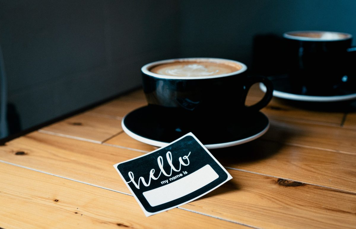 blank nametag beside a coffee cup for someone with deed poll