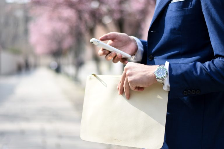 man holding deed poll in one hand and phone in another